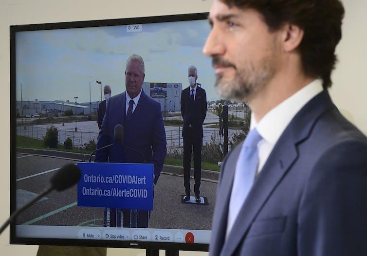 Justin Trudeau parle lors d'une conférence de presse tandis que Doug Ford apparaît sur un écran à côté de lui.