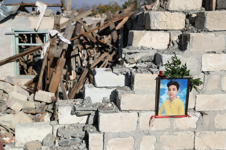 Rubble of a cement home and photo of a boy with flowers around it