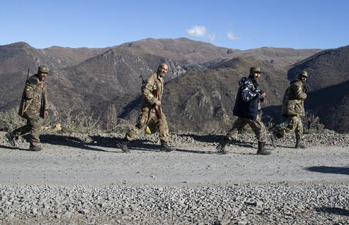 Servicemen in fatigues walk along a gravel road with tower mountains in the background