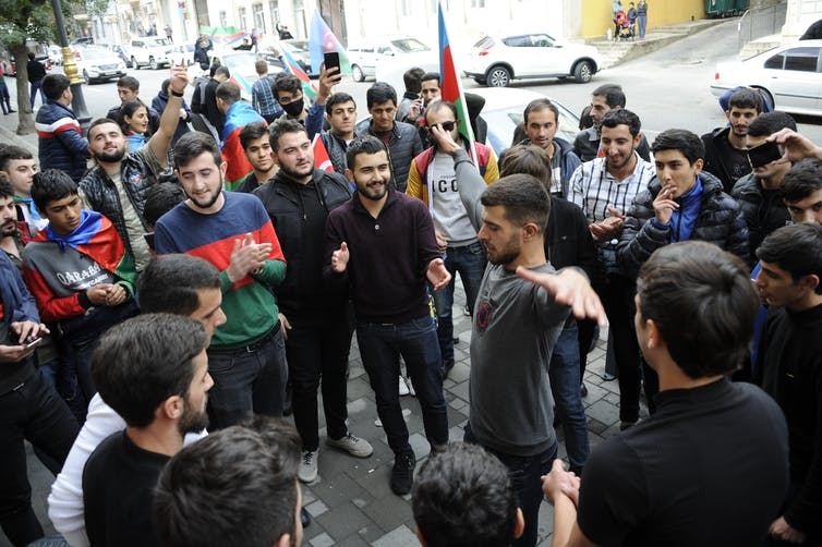 A group of Azeri men stand by as one performs a celebration dance.