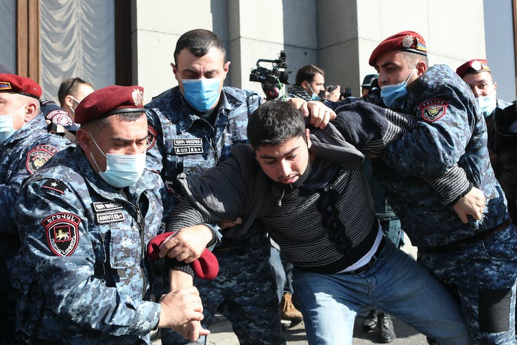 A group of Armenian security officers detain a protestor.