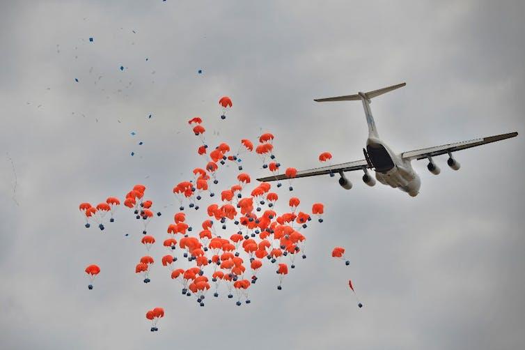 Un avion effectue un largage d'aide alimentaire