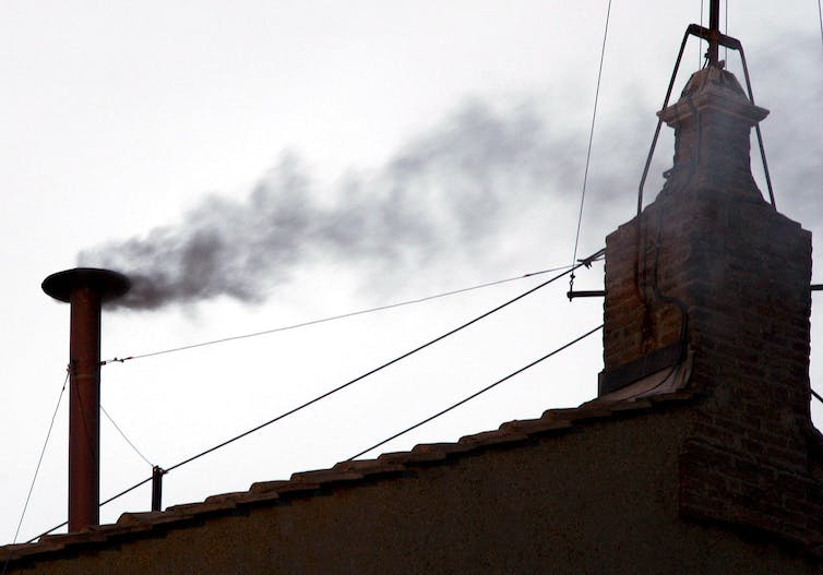 Black smoke pours out of a chimney on the Vatican roof as cardinals canvass for the next pope.