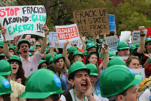 Protesters shouting, holding anti-fracking signs