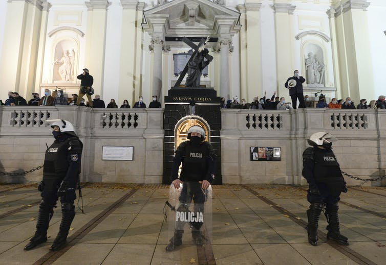 Members of a far-right organization stand guard in front of the Holy Cross Church, fronted by a row of police officers, in Warsaw on Oct. 28, 2020