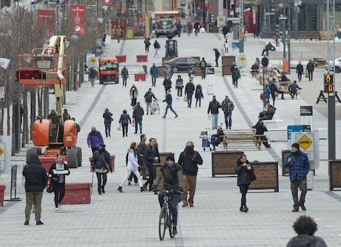 Des piétons et des cyclistes circulent sur la rue Sainte-Catherine à Montréal