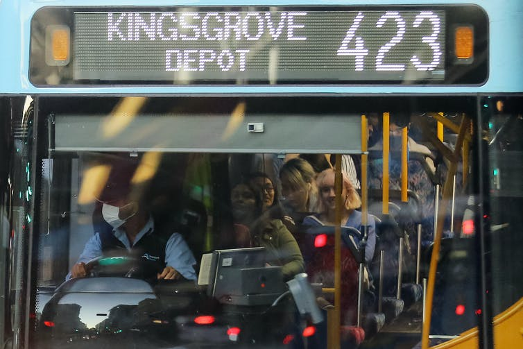 People crowd onto a bus in Sydney.