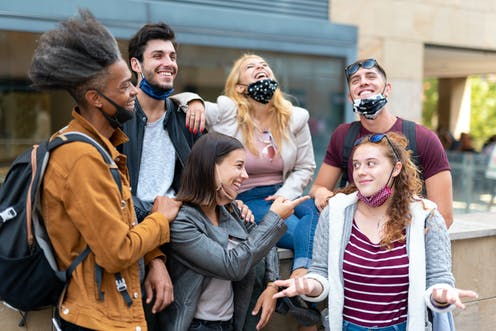 Group of young people stood close talking with masks worn on their chins.