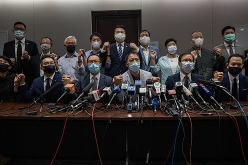 Group of Hong Kong opposition MPs wearing masks and holding hands, in front of microphones