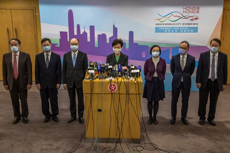 Carrie Lam stands at podium with microphones surrounded by six colleagues, all wearing masks.