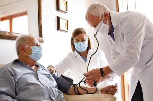 Médicos tomando la tensión a un paciente mayor.