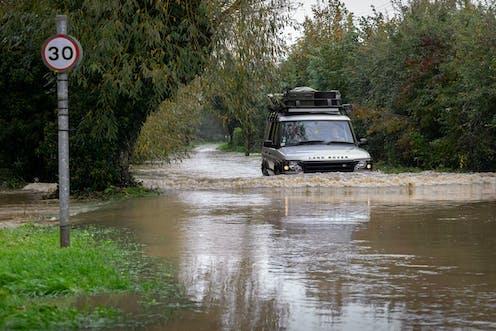 A Land Rover car drives along a flooded street.