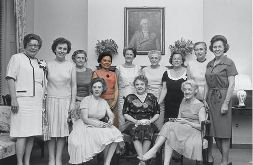 Black and white group photo of the 1960 female congressional class with Patsy Mink in color