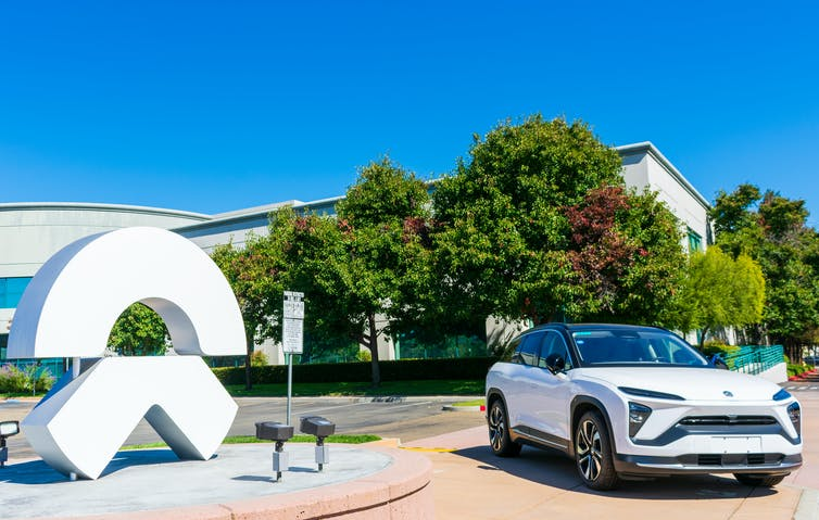 A NIO car parked outside next to a statue of the firm's logo
