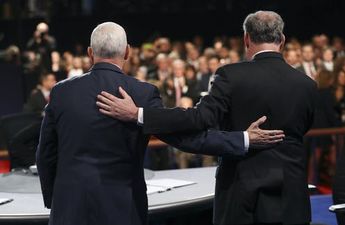 Mike Pence and Tim Kaine stand holding each other's backs at a debate