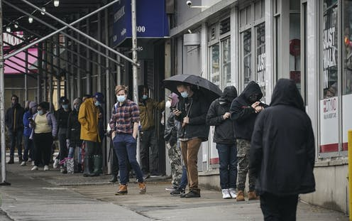 People wearing masks wait in line to get a coronavirus test in New York City.