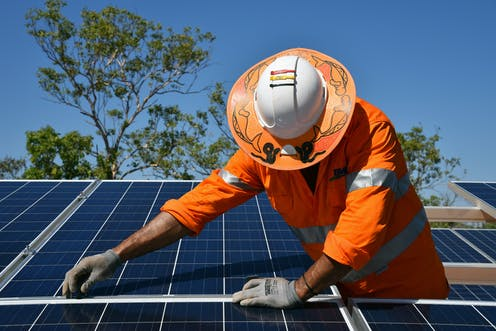 Worker installing solar panels in Daly River, Northern Territory.