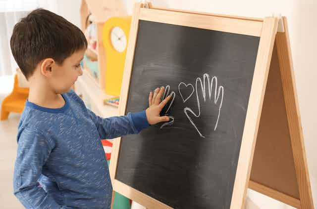 A young boy traces his hand on a blackboard.