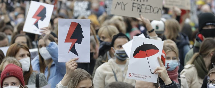 Women's rights activists with posters of the Women's Strike symbol protest in Warsaw, Poland, in October 2020 against a further tightening of Poland's already restrictive abortion laws