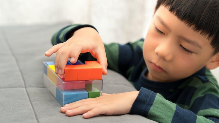 A boy plays with blocks.