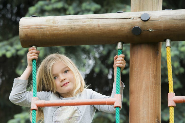 A girl on play equipment.
