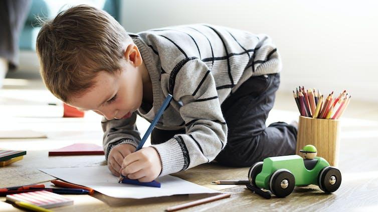 A boy draws on paper.