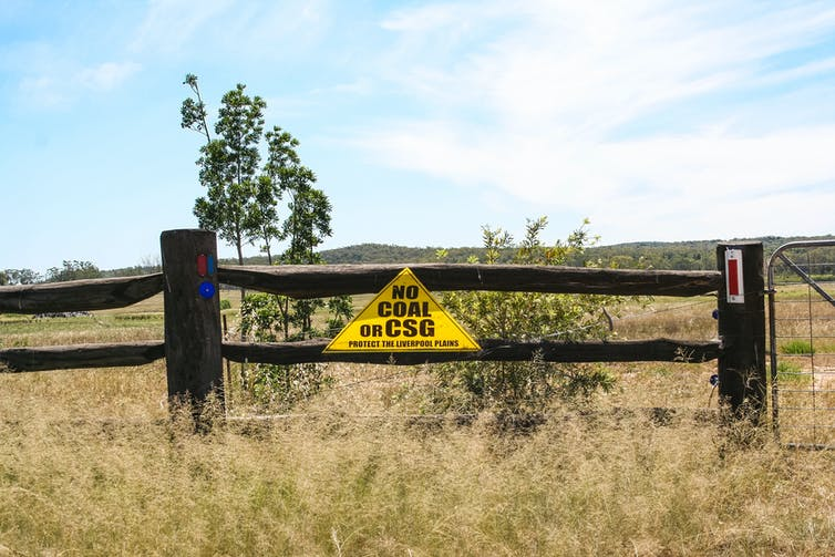 A yellow triangle sign that says 'no coal or coal seam gas' on a wooden fence.
