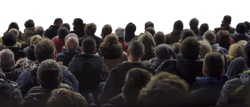 Grupo de personas de espaldas mirando a un fondo blanca.