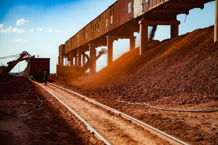 Machines load a train cart with minerals in an open-cast bauxite mine.
