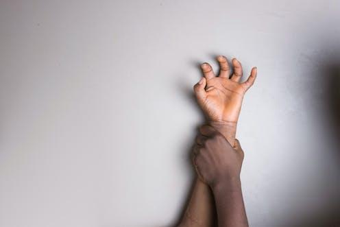 Una mano de hombre aprisiona contra una pared el brazo de una adolescente.