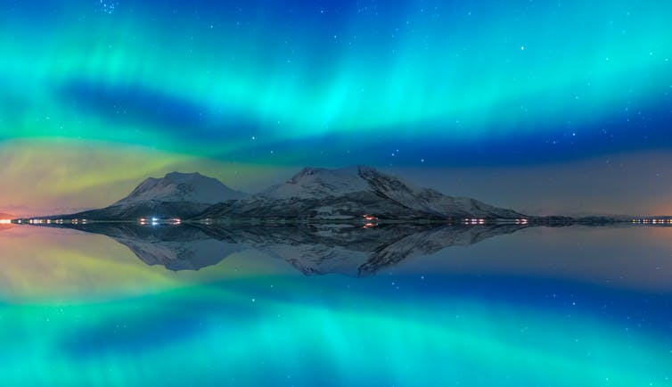 A band of turquoise light in the sky is reflected in the Norwegian fjord below.