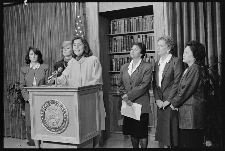 Black and white image of six congresswomen in suits standing at a lectern