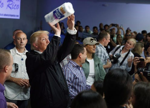 Donald Trump hold a paper towel roll like a football ready to toss to the crowd. Journalists look on.