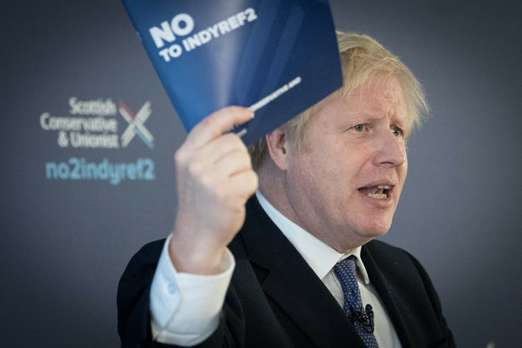 Boris Johnson waves a pamphlet for the campaign against a second Scottish independence referendum.