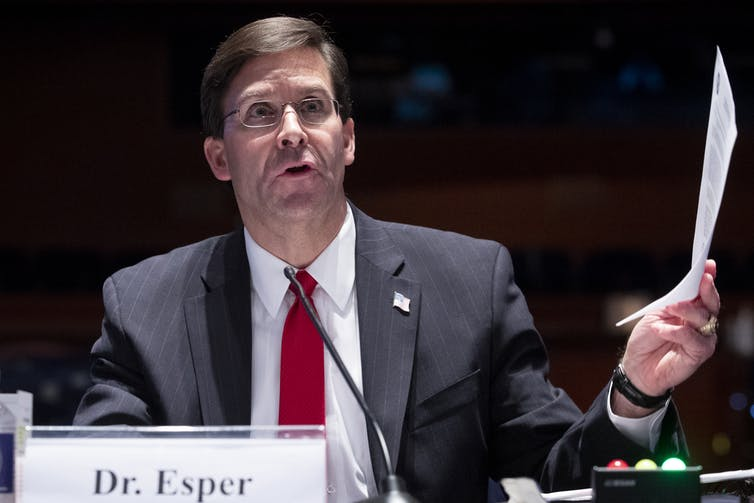Esper testifying in Congress, holding a piece of paper