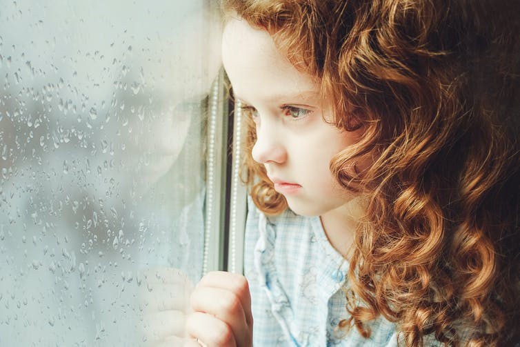 A girl looks out of a window.