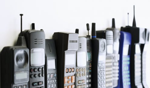 A row of old cellular phones from the 80s and 90s.