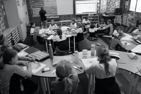 Students in a classroom with different furniture options like ottomans, and no 'front' of the class.