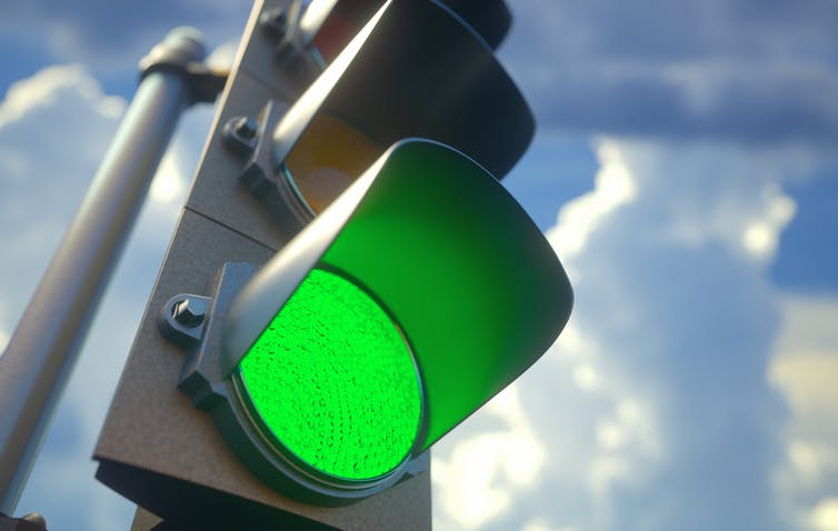 Green traffic light against backdrop of cloudy sky