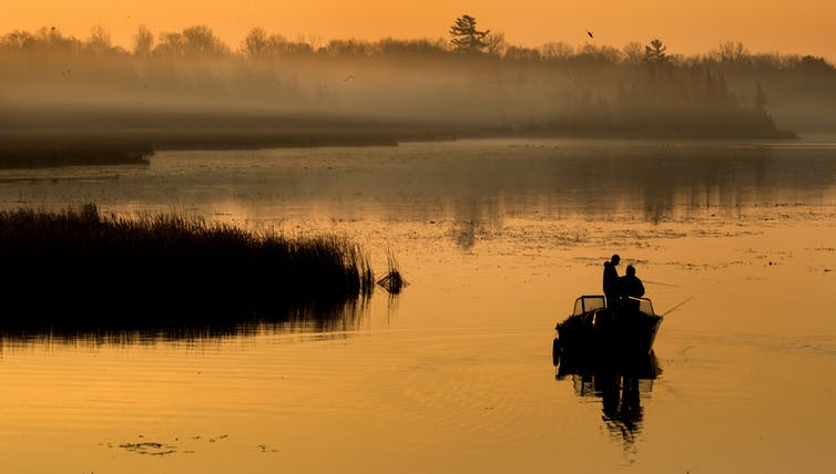 Men fish from a boat as the sun rises.