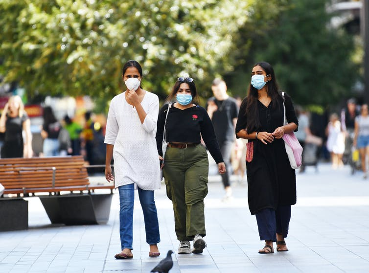 Three women walk through Rundle Mall wearing masks.