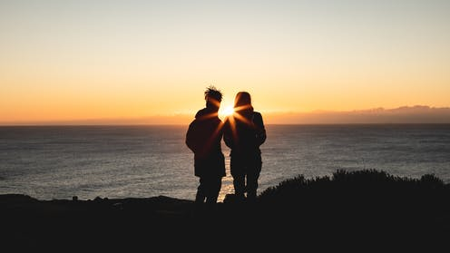 Couple watching the Sun rise over the ocean