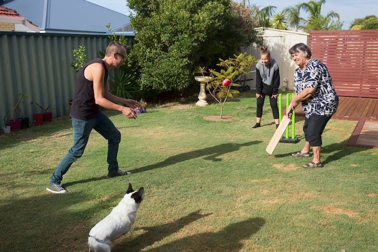 A family play cricket in the back yard