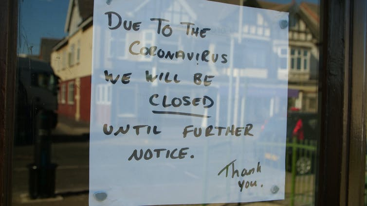 A cafe sign states it is closed due to coronavirus.