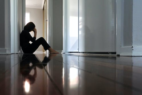 Woman sitting on the floor at home, appears depressed.