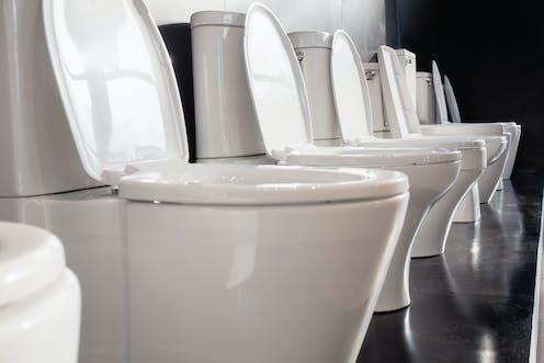 Row of white ceramic toilet bowls on black wall.