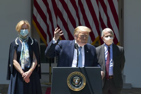 Donald Trump flanked by scientists Deborah Birx and Anthony Fauci.