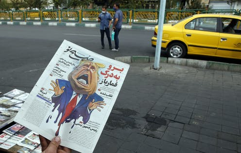 Man holding Iranian newspaper with caricature of Donald Trump on front page.