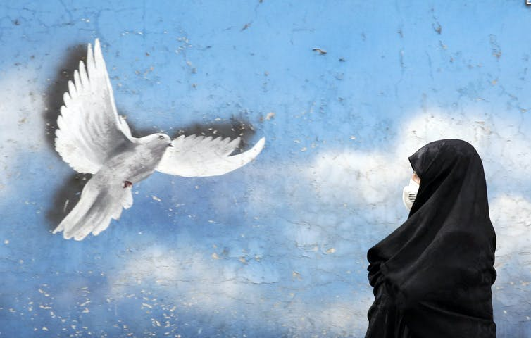 Woman in a chador walks past a mural of a peace dove in Tehran, November 2020.