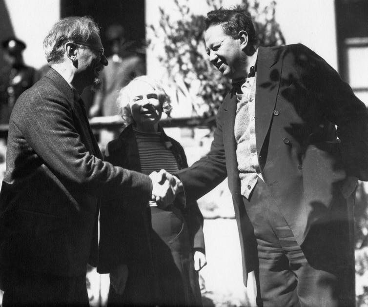 Black and white image of Trotsky and River shaking hands, with a smiling Sedova next to them